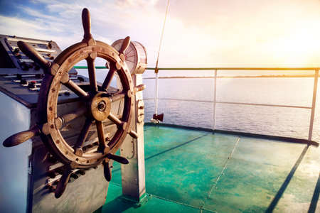 deck: Wooden wheel on the ship at sunset on Issyk Kul lake Stock Photo