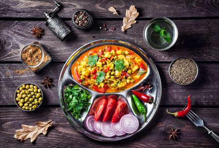 verduras verdes: Mutter paneer plato indio con las especias en el fondo de madera