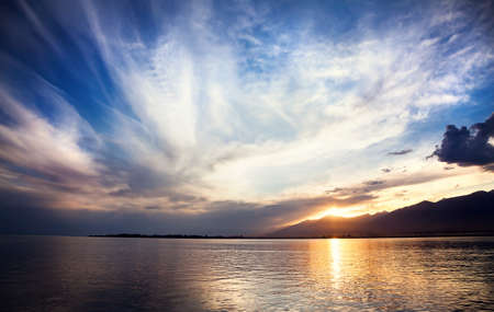 ata: Issyk Kul lake at sunset cloudy blue sky in Cholpon Ata, Kyrgyzstan Stock Photo