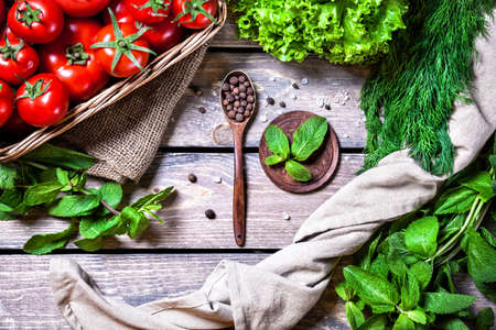 ensalada: Cuchara con pimienta negro, tomate, hierbas y ensalada verde en la mesa de madera en la cocina