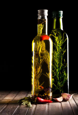 Bottle with oil, herbs and spices on black background