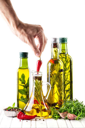 tarragon: Man putting red chili in the bottle with oil, herbs and spices on white background Stock Photo