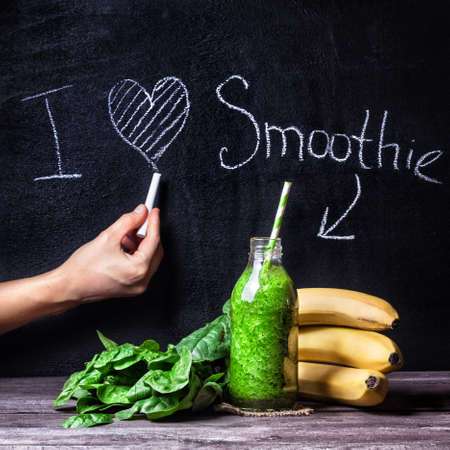 writing board: Fresh green smoothie with banana and spinach with title I love smoothie on blackboard
