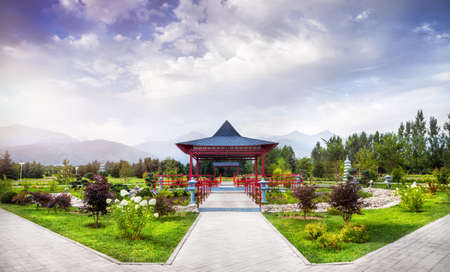 parks: Japanese garden with red pagoda at mountains and blue sky in dendra park of first president in Almaty, Kazakhstan