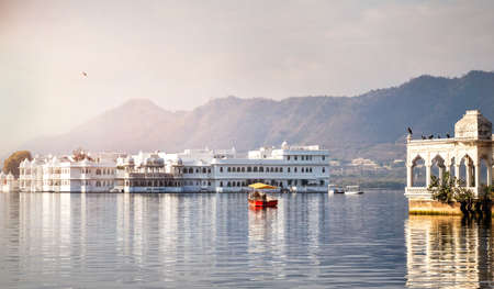 boat house: White palace and boat on Lake Pichola in Udaipur, Rajasthan, India Stock Photo