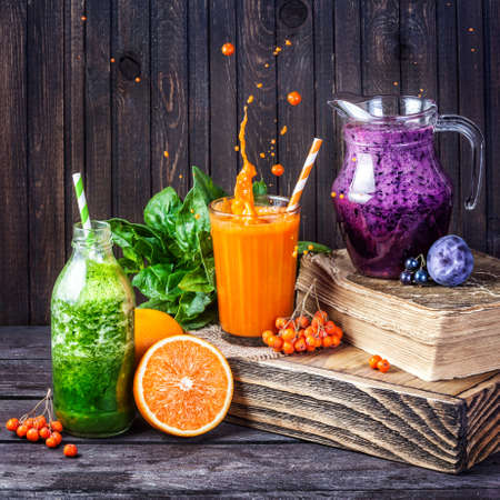 nutrition: Fresh juice and smoothies with berries, fruits and green spinach on wooden background