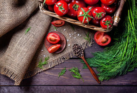 ensalada tomate: Cuchara con pimienta negro, tomate, hierbas sobre la mesa de madera Foto de archivo