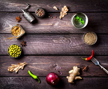 Spices and ingredients for the dish on the wooden background with space for text
