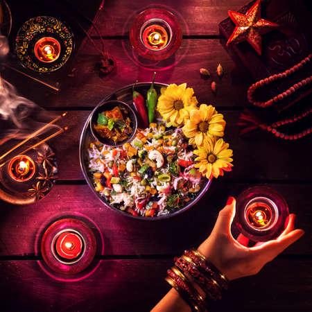 Vegetarische biryani, kaarsen, wierook en religieuze symbolen op Diwali viering op de tafel Stockfoto