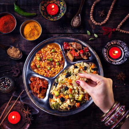 kerze: Frau isst vegetarisch Biryani durch ihre Hand mit Armreifen in der Nähe von Kerzen, Weihrauch und religiöser Symbole in Diwali Feier