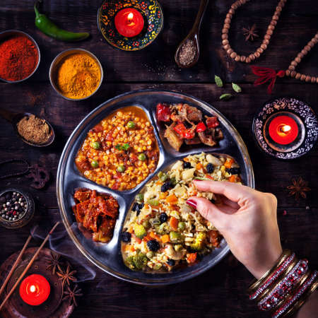 indian food: Woman eating vegetarian biryani by her hand with bangles near candles, incense and religious symbols at Diwali celebration