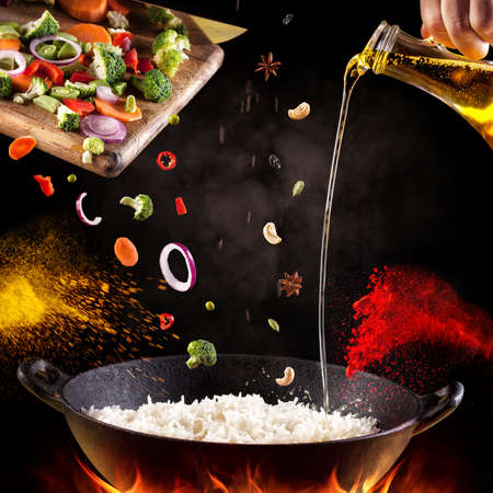 épices: Biryani indienne végétarienne avec des légumes et des épices dans le processus de cuisson sur fond noir