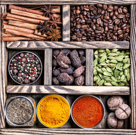 Spices, coffee and walnuts in the wooden box Фото со стока