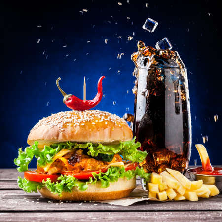 Veggie burger, French fries, ketchup and ice cubes falling in cola glass