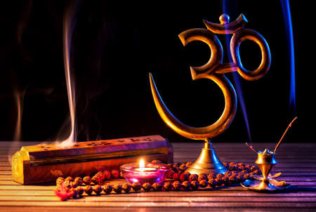 indian festival: Om symbol, incense smoke, candle and japa mala on wooden table at black background