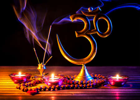 Om symbol, incense smoke, candle and japa mala on wooden table at black background