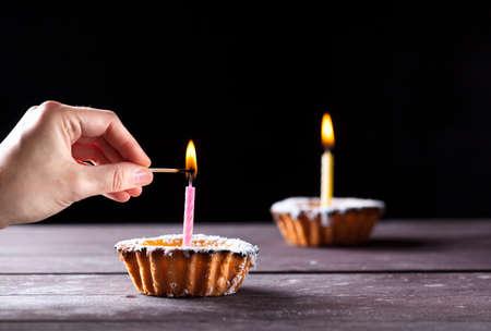 streichholz: Hand-Anwendung Übereinstimmung mit einer Kerze auf Käsekuchen auf schwarzem Hintergrund