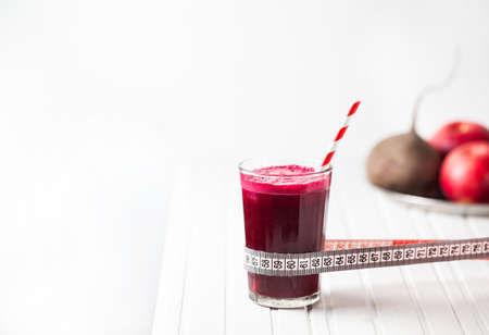juice fresh vegetables: Fresh beetroot and apple juice in the glass with tape measure on white wooden background with space for text Stock Photo