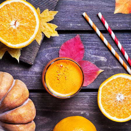 Fresh pumpkin and oranges juice on wooden background in autumn season Stock Photo - 47040471