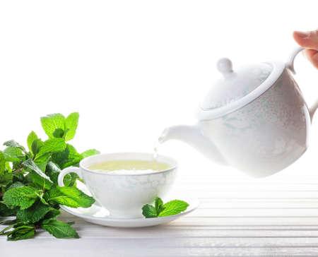 taza de té: Té de menta derramamiento de la tetera en la taza cerca de hojas de menta en el fondo blanco