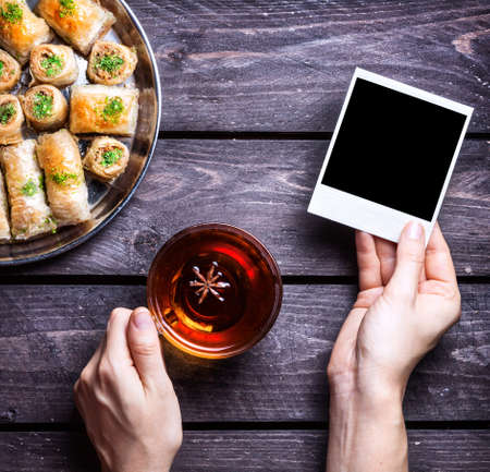 turkish people: Hands with blank photo frame and badyan tea near Turkish baklava on wooden background Stock Photo