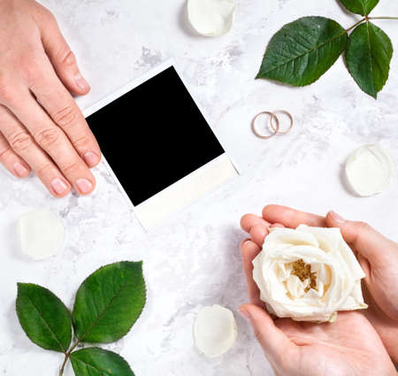 Blank photo frame, two wedding rings, bride and groom hands on white marble background photo