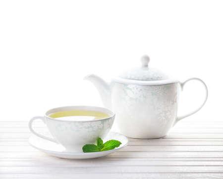 taza de té: Té de menta en la taza cerca de la tetera en el fondo blanco