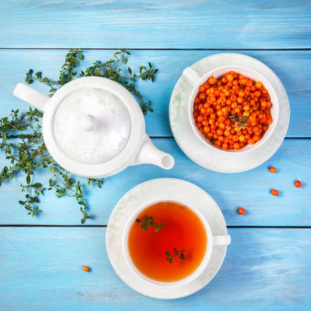 buckthorn: Herbal and berry tea in the cup near teapot and thyme leaves on blue wooden background