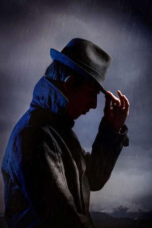 Man in zwarte hoed in de regen op donkere bewolkte hemel Stockfoto