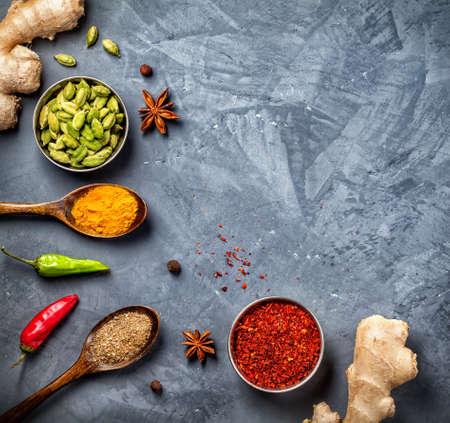 Ginger, chili peppers, cardamom, powder spices in spoons on grunge background Stock Photo