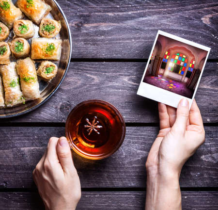turkish dessert: Hands with photo of Rajasthan palace and badyan tea near Turkish baklava on wooden background