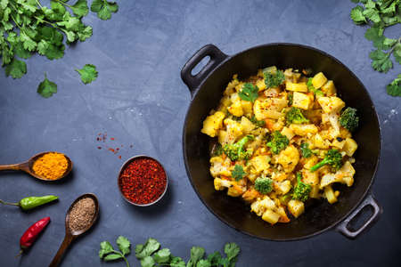 ジャガイモ、カリフラワー、テクスチャ グランジ背景にスパイスが付いているインドじゃがいもゴビ皿