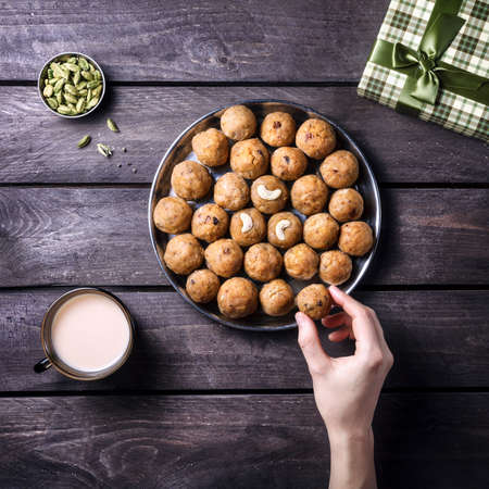 Indian Besan Ladoo sweet dessert with green cardamom on wooden background at festival time