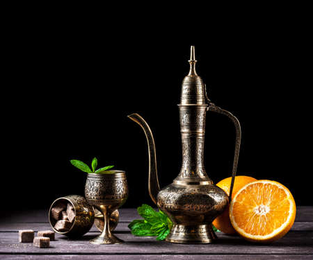 cooper: Moroccan tea with mint and oranges in oriental cooper pot and cups on rustic wooden background
