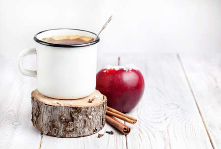 Hot beverage from apples and spices on white wooden background at Christmas time