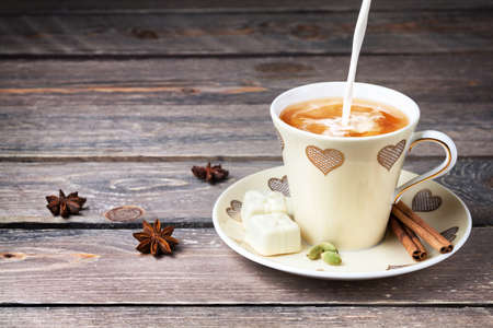 Indian Masala tea with milk, cinnamon, star anise and cardamom spices in cup with hearts on wooden table Standard-Bild