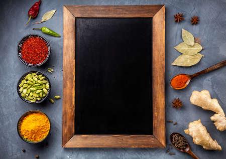 pimenton: Varias especias como la cúrcuma, el cardamomo, el chile, pimentón, jengibre, anís y clavo de olor cerca de la pizarra en el fondo del grunge. Espacio libre para el texto