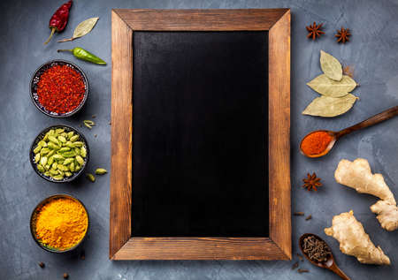 Various Spices like turmeric, cardamom, chili, paprika, ginger, star anise and clove near blackboard on grunge background. Free space for your text Standard-Bild