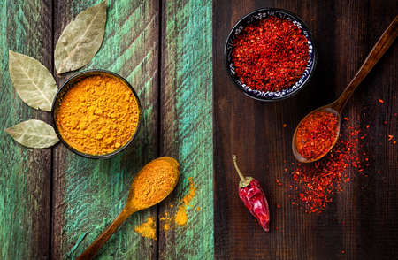 turmeric: Chili, paprika, turmeric and bay leaves on wooden green and brown background Stock Photo