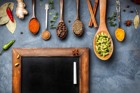 Various Spices like turmeric, cardamom, chili, ginger, star anise and cinnamon near blackboard on grunge background. Free space for your text