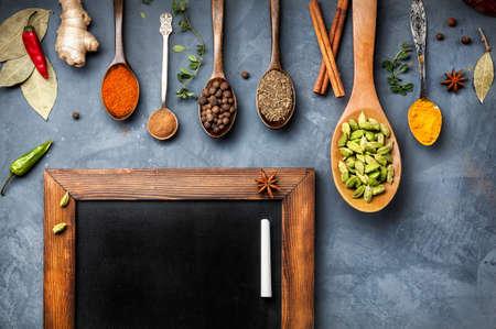 Diverse kruiden zoals kurkuma, kardemom, chili, gember, steranijs en kaneel dichtbij bord op de grunge achtergrond. Vrije ruimte voor uw tekst
