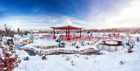 chinese garden: Winter Japanese garden with red pagoda at mountains and blue sky in dendra park of first president in Almaty, Kazakhstan