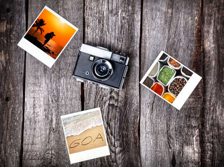 Old film camera and photos with Goa tropical beaches and spices on the wooden background photo