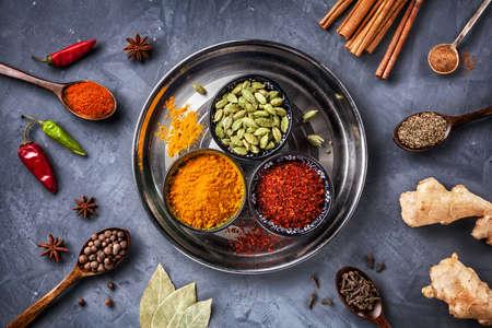 Diverse kruiden zoals kurkuma, kardemom, chili, bayberry, laurier, paprikapoeder, gember, kaneel, komijn, steranijs en kruidnagel op grunge achtergrond