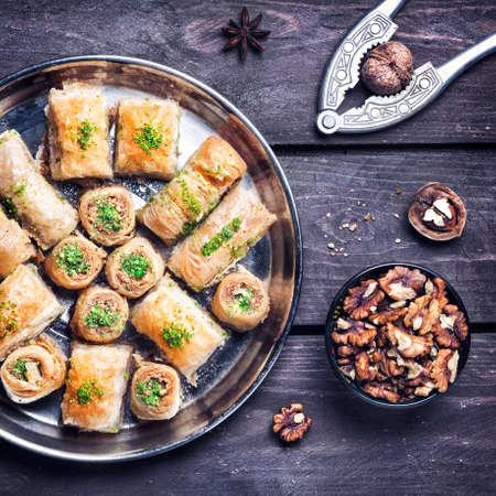 Turkish baklava near walnuts and nutcracker on wooden background