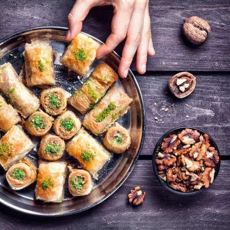 Hand holding Turkish baklava near walnuts on wooden background 写真素材