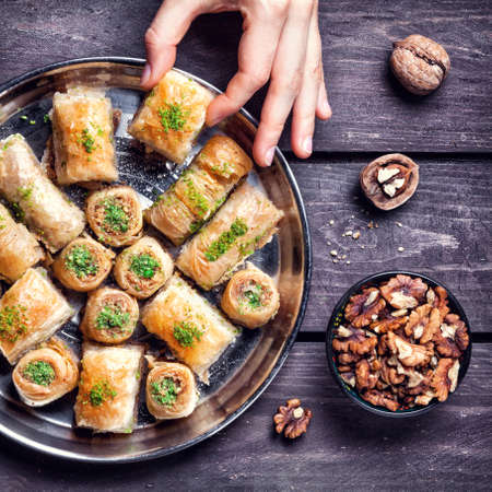 culinary tourism: Hand holding Turkish baklava near walnuts on wooden background Stock Photo
