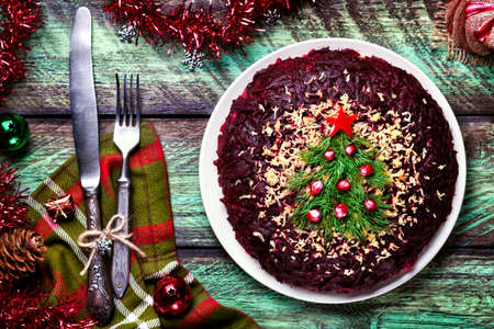 pomegranates: Vegetable salad from beetroot with Christmas tree decoration on the green table at New Year time Stock Photo