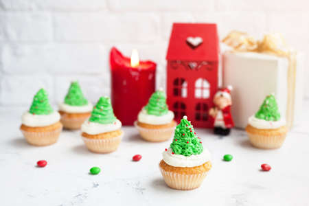 delight: Green tree cupcakes near red house, candle and present at Christmas time Stock Photo
