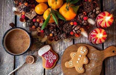 Kerst zelfgemaakte ontbijtkoek koekjes, warme chocolademelk en kaarsen op houten tafel